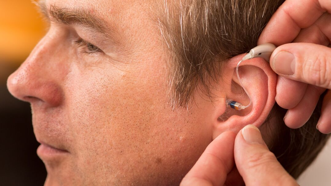 A man being fitted with an in-ear hearing aid