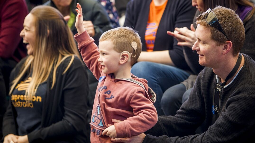 A child with a cochlear implant raising their hand in a crowd