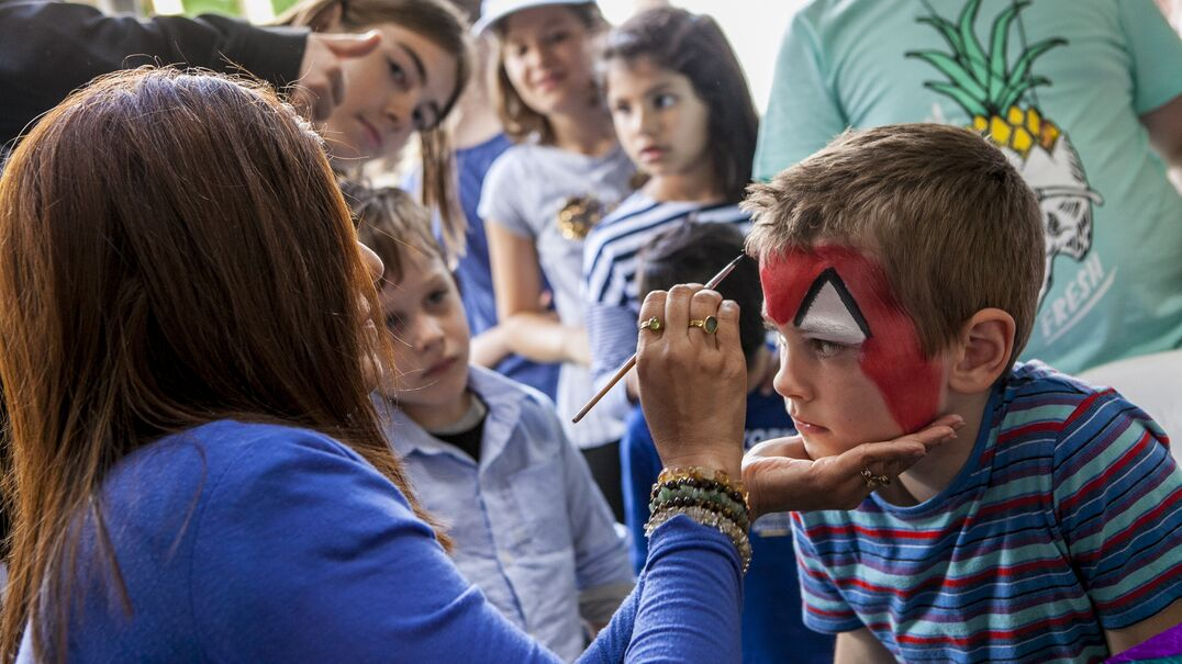 A boy having his face painted in front of a crowd of other children