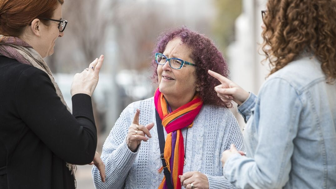 Three women engaged in conversation using Auslan