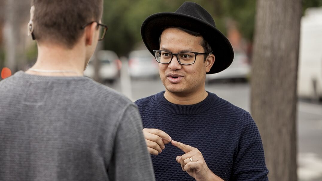 A man in a hat and glasses signing to a man in a jumper