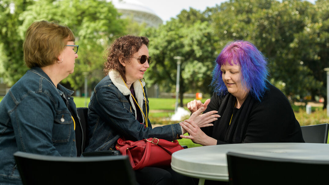 Three women in a park, two are communicating with tactile signs