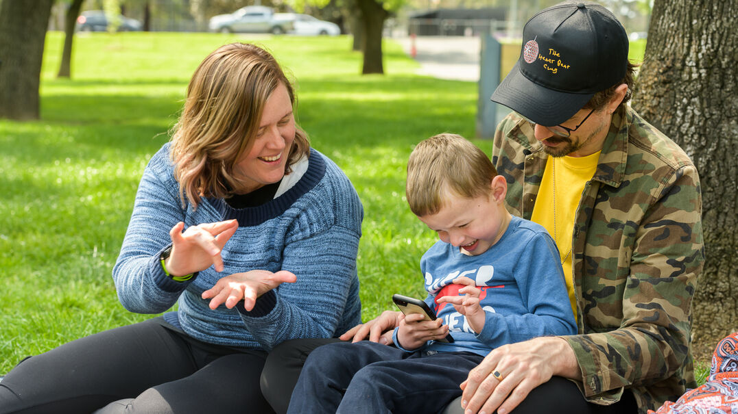 Parents showing their son how to use a phone app in a park